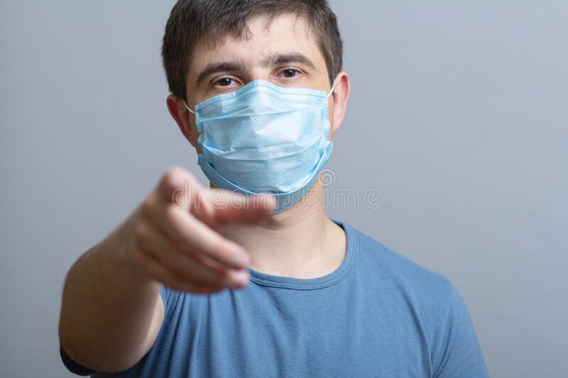 Young man in a protective medical mask showing finger at you, quarantine measures, doctor looking at you, concept of health and. Personal responsibility stock image
