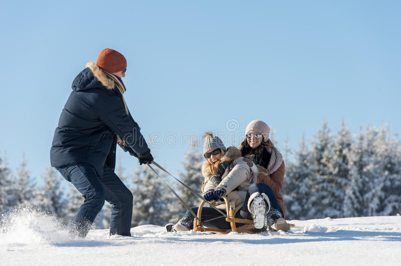 Young man pulling girls on winter sledge royalty free stock images
