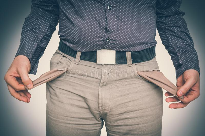 Man pulling out empty pockets - poor people concept stock photos