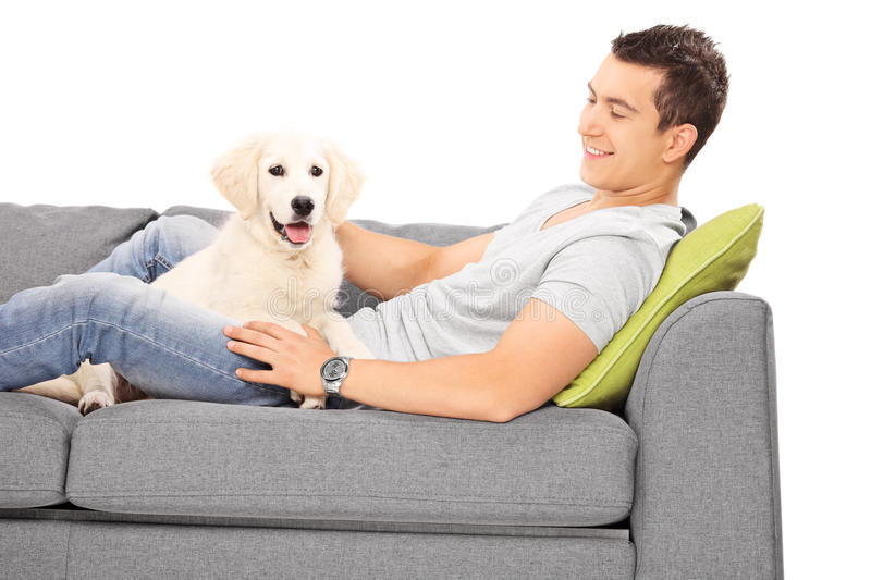 Download Young Man And A Puppy Lying On Couch Stock Photo - Image: 43039648