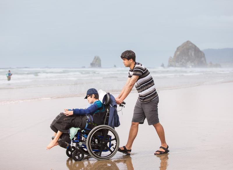 Young man pushing disabled brother in wheelchair on beach stock image