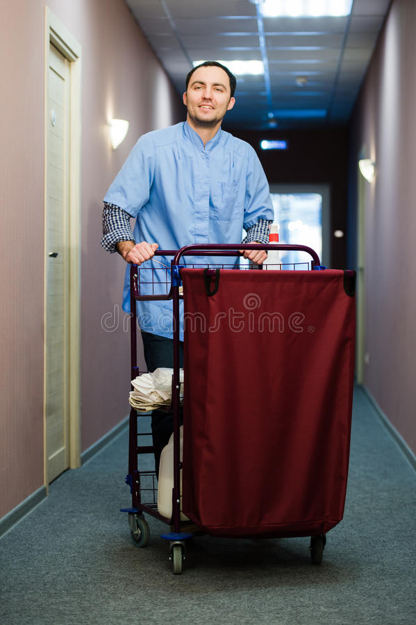 Young man pushing a housekeeping cart laden with clean towels, laundry and cleaning equipment in a hotel as he services. The rooms stock photos