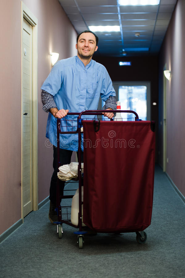 Young man pushing a housekeeping cart laden with clean towels, laundry and cleaning equipment in a hotel as he services. The rooms stock image