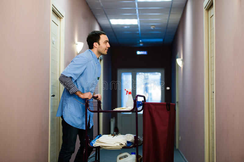Young man pushing a housekeeping cart laden with clean towels, laundry and cleaning equipment in a hotel as he services. The rooms royalty free stock photography