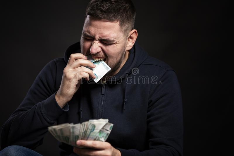 A young man puts money in his mouth. Fear and depression. Black background royalty free stock photos