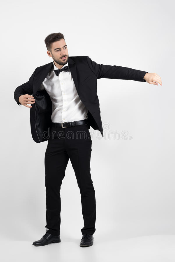 Young man putting on black suit tuxedo coat. stock photos