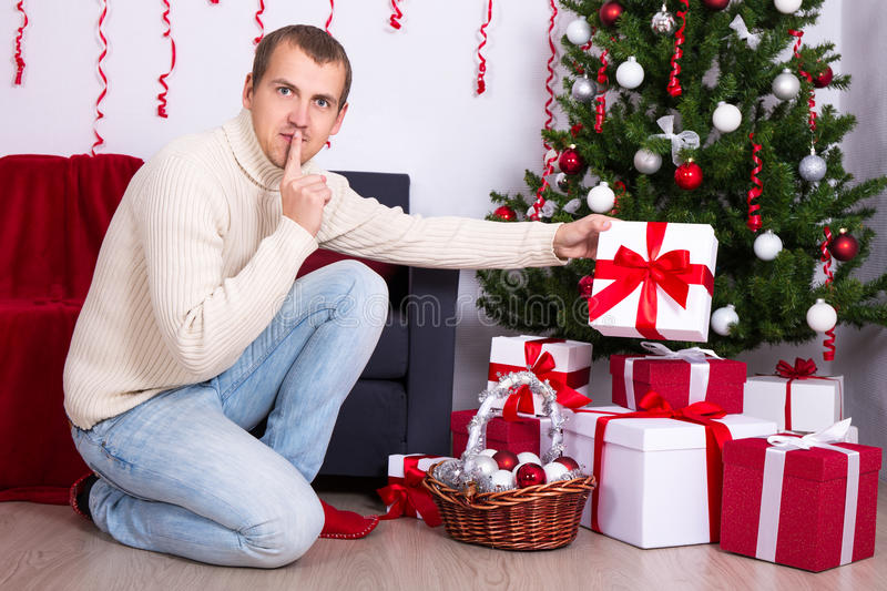 Young man putting christmas present box under christmas tree. Christmas concept - young man putting christmas present box under christmas tree stock photo