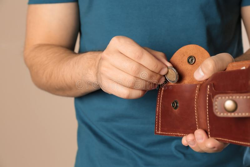 Young man putting coin into wallet on beige background. Space for text. Young man putting coin into wallet on beige background, closeup. Space for text stock photo
