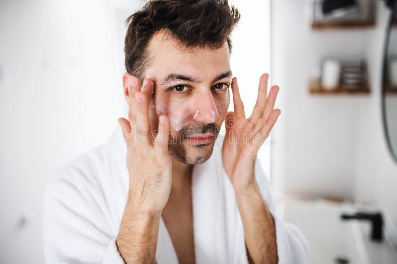 Young man putting cream on face in the bathroom in the morning, daily routine. Young man putting cream on face in the bathroom in the morning, a daily routine royalty free stock photo