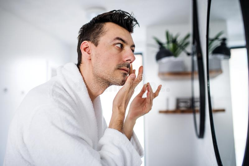 Young man putting cream on face in the bathroom in the morning, daily routine. Young man putting cream on face in the bathroom in the morning, a daily routine royalty free stock photos
