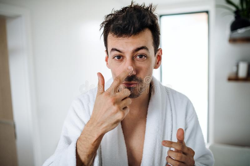 Young man putting cream on face in the bathroom in the morning, daily routine. Young man putting cream on face in the bathroom in the morning, a daily routine stock photo