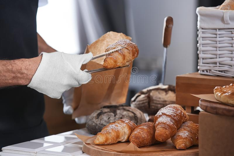 Young man putting croissant in paper bag with tongs in bakery stock photography