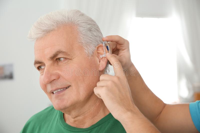 Young man putting hearing aid in father`s ear. Indoors stock image