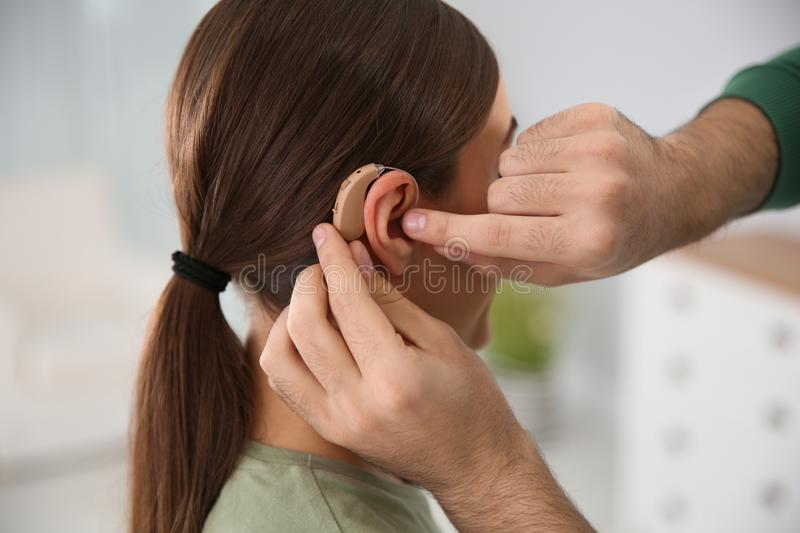 Young man putting hearing aid in woman`s ear. Indoors stock photography