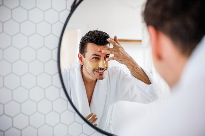 Young man putting mask on face in the bathroom in the morning, daily routine. Young man putting mask on face in the bathroom in the morning, a daily routine royalty free stock images