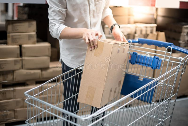 Young man putting paper box into trolley cart in warehouse royalty free stock photo