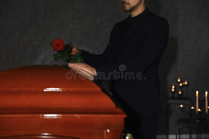 Young man putting red rose onto casket lid in funeral home, royalty free stock photo