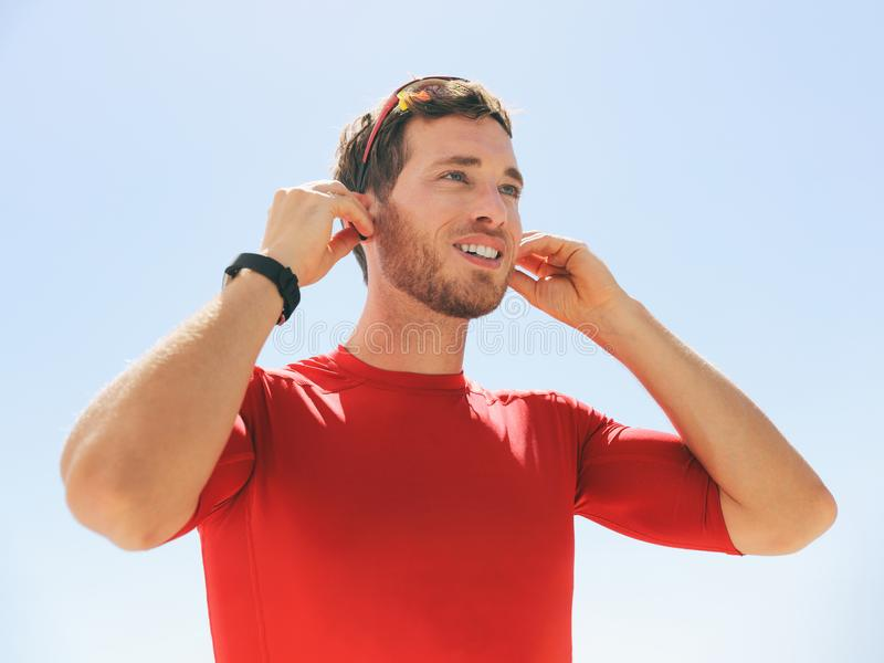 Young man putting on wireless headphone bluetooth connected to smartwatch earphones for fitness run outdoors. Happy active person stock photo