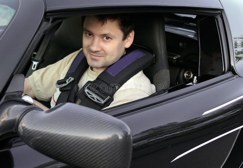 Young man, racer sitting in sport car stock photography