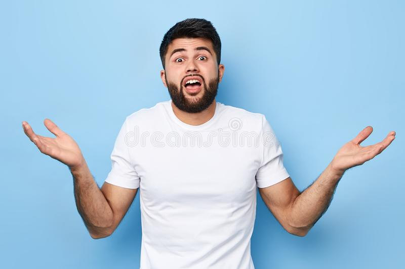 Young man with raised shoulders, showing ignorance on a blue background royalty free stock photography