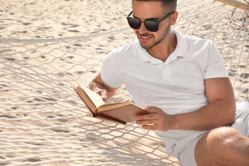 Young man reading book in hammock on royalty free stock photo