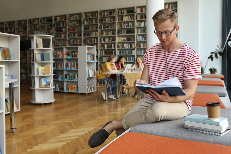 Young man reading book in library royalty free stock photo