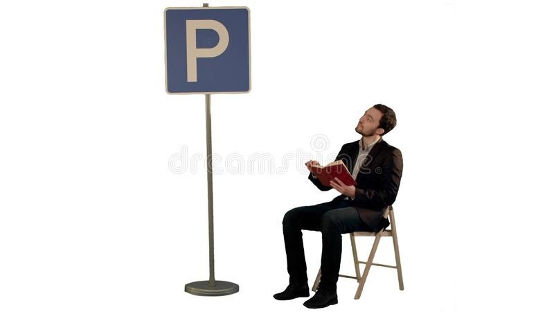 Young man reading a book near parking sign on white background isolated royalty free stock images