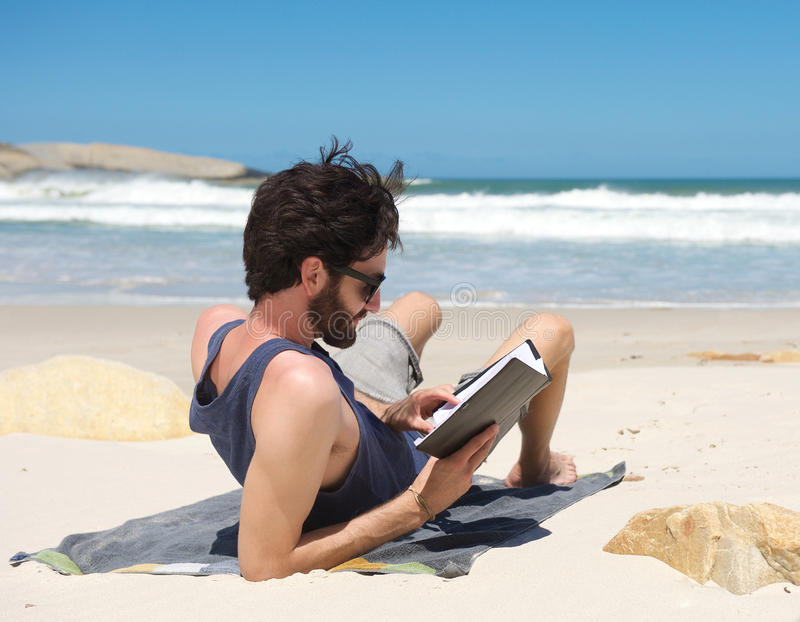 Young man reading book on secluded beach. Portrait of a young man reading book on secluded beach stock photos