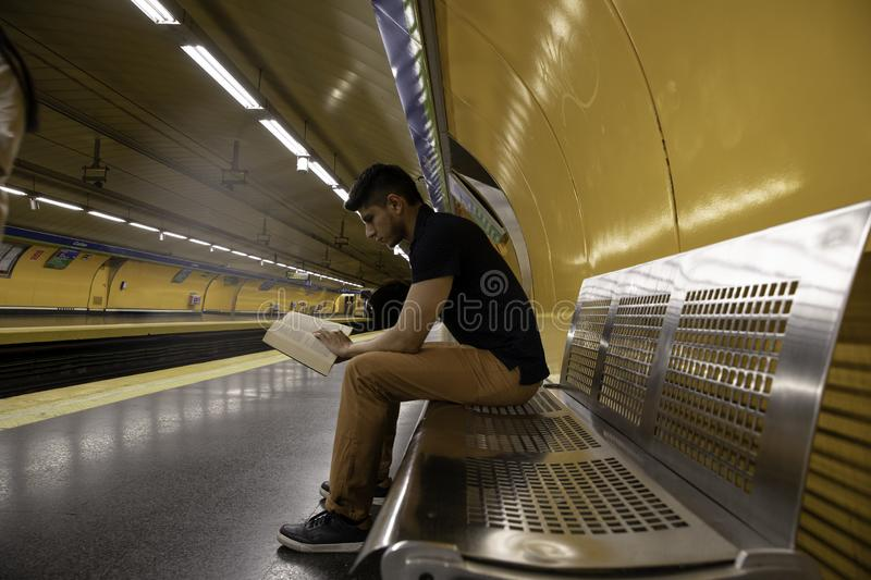 Young man reading a book at the subway station stock image
