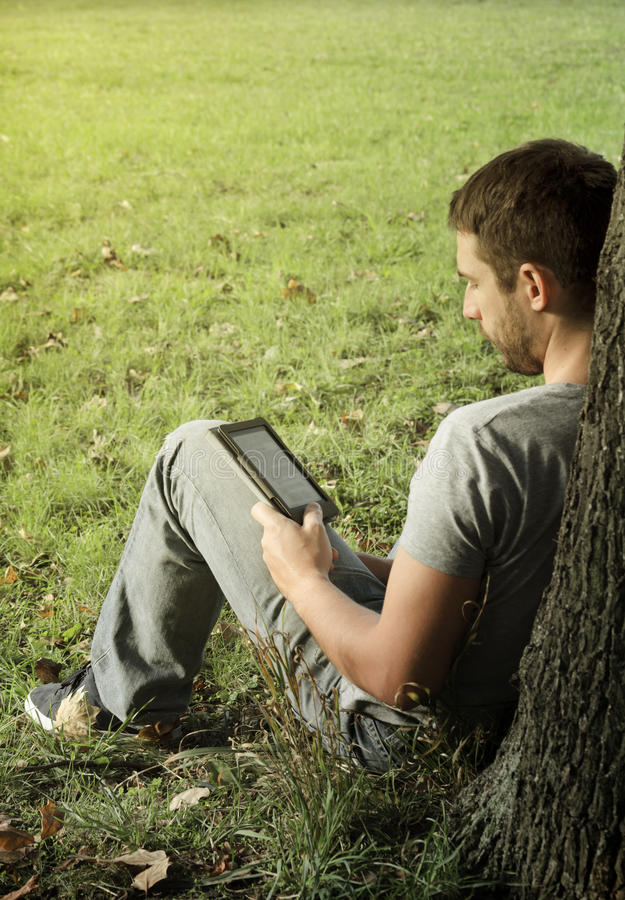 Download Young man reading e-book stock photo. Image of ebook - 34327830