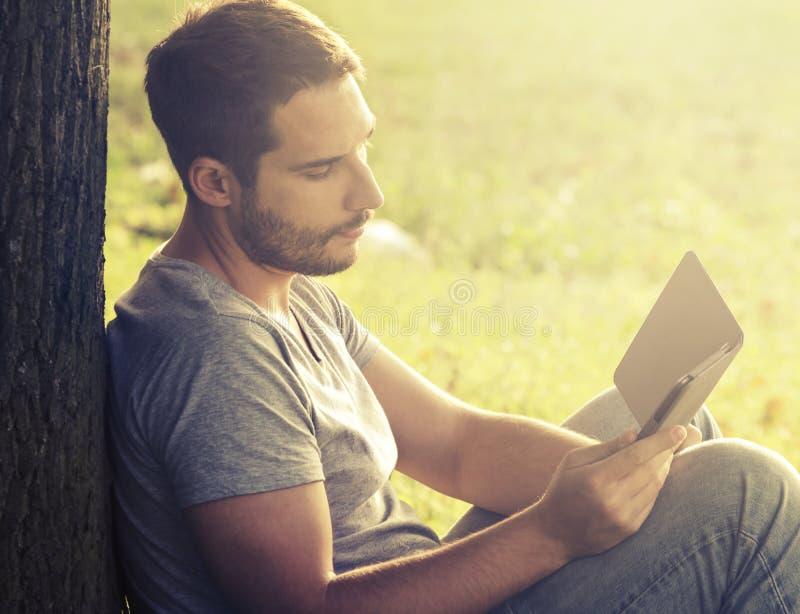 Young man reading e-book stock photography