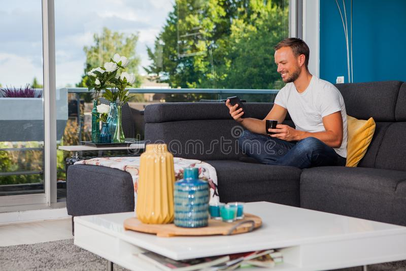 Young man reading from an ebook reader while drinking coffee on the couch stock image
