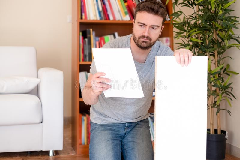 Man portrait and do it yourself furniture assembly. Young man reading the instructions to assemble furniture royalty free stock image