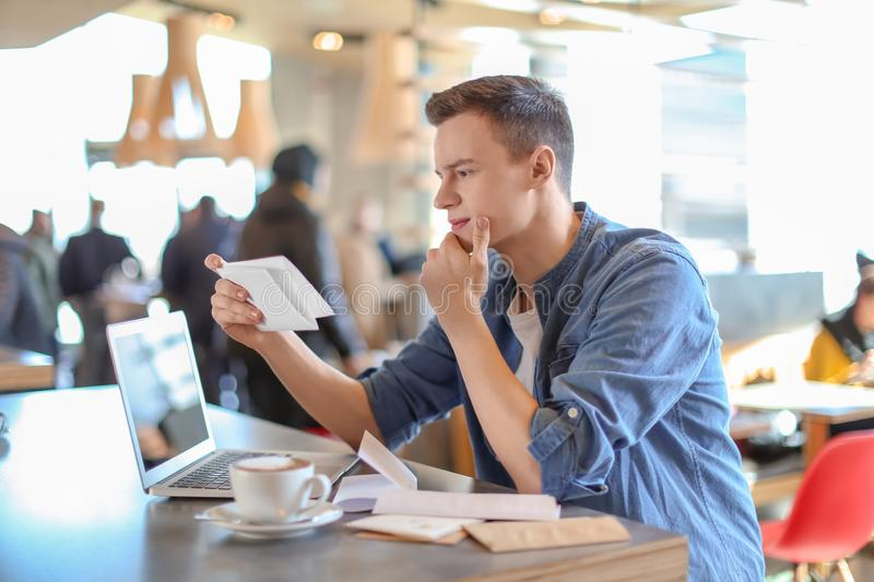 Young man reading letter at table in cafe. Mail delivery royalty free stock photography