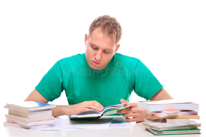 Young man reading literature at the desk stock images
