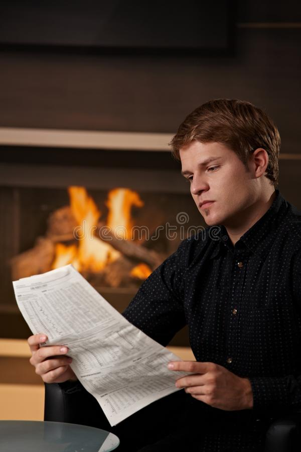 Young man reading newspaper royalty free stock image