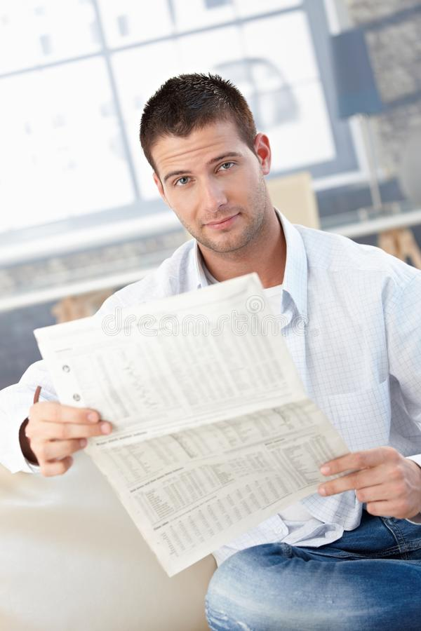 Young man reading newspaper on sofa stock photography