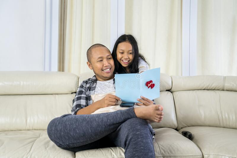 Young man reads a greeting card from his daughter royalty free stock images