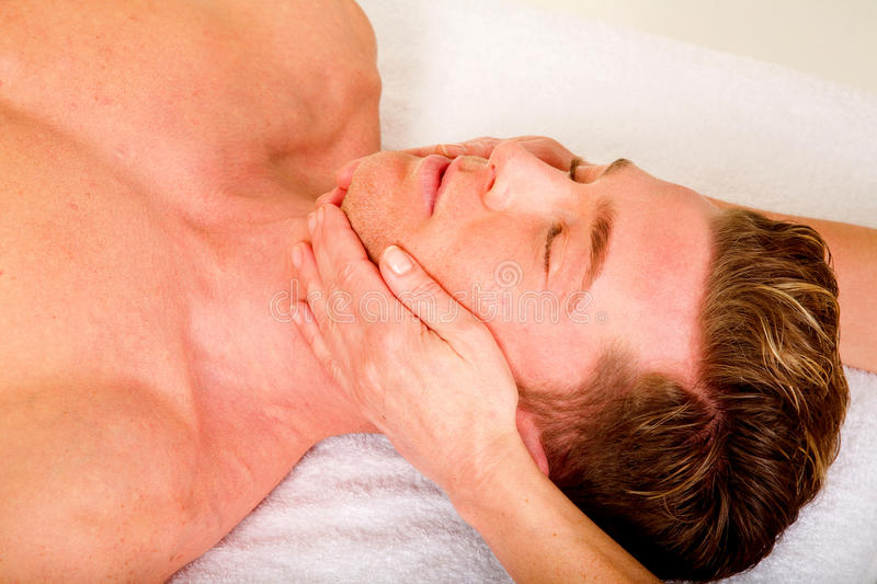 Young man receives a face massage stock photo