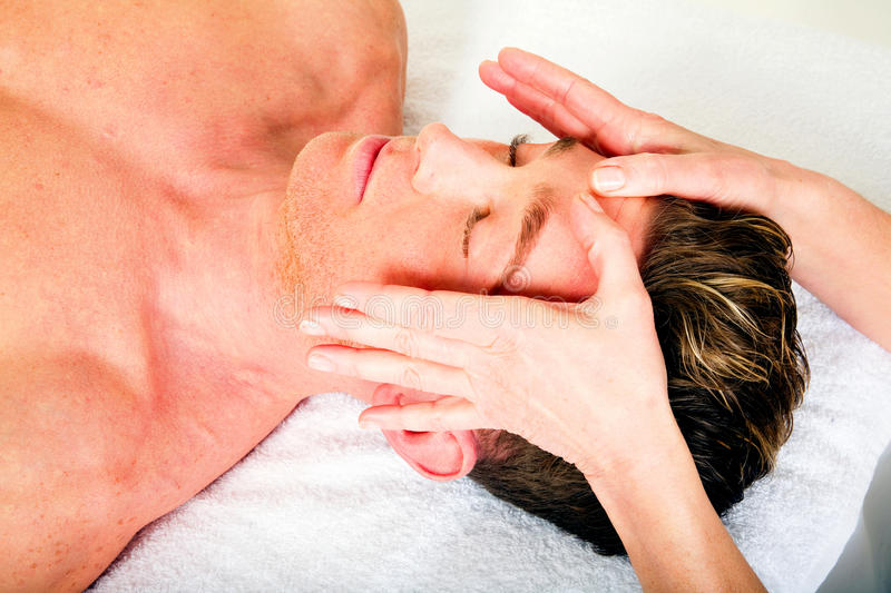 Young man receives a face massage royalty free stock image