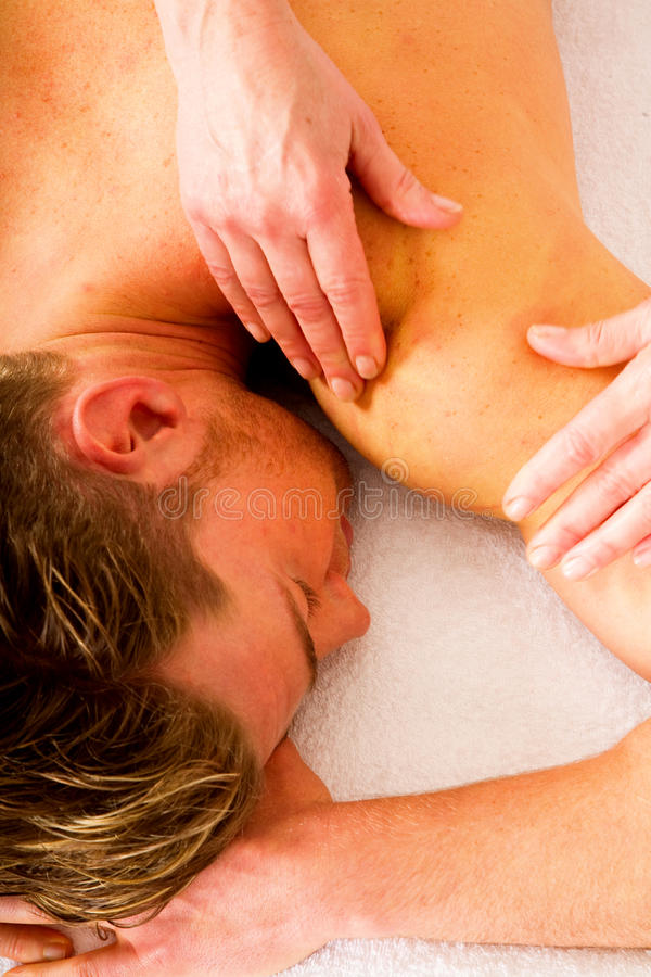 Young man receives massage stock photography