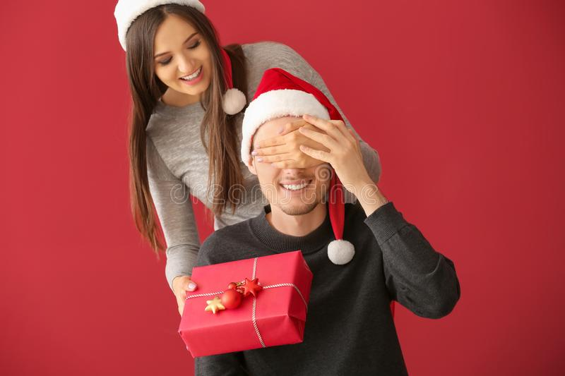 Young man receiving Christmas gift from his wife on color background stock photos