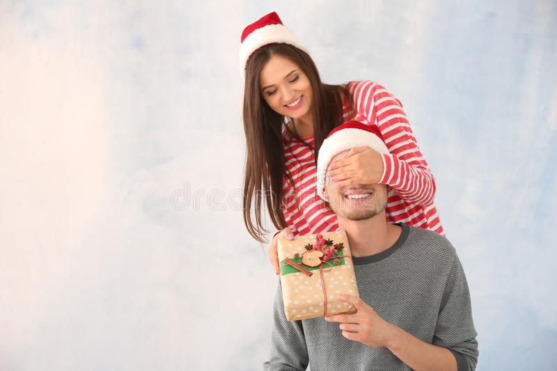Young man receiving Christmas gift from his wife on light background stock photography