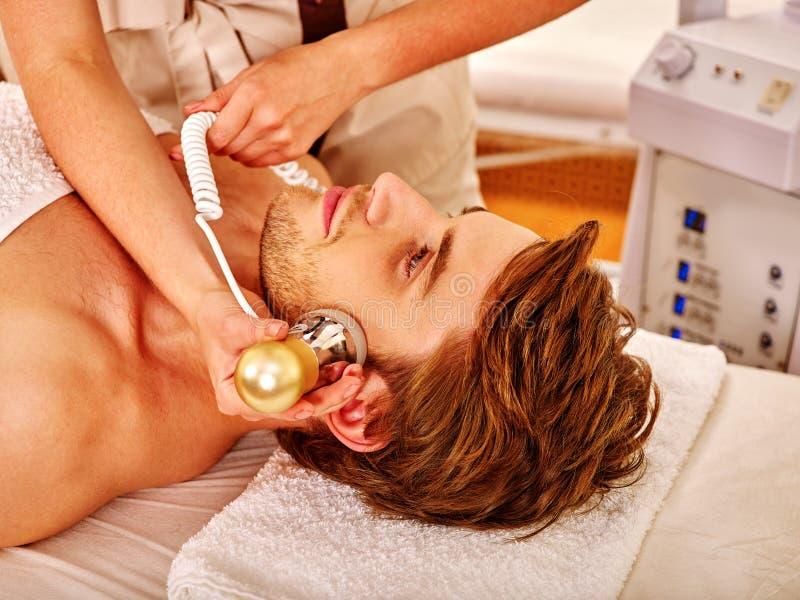 Young man receiving electric facial massage. stock photos