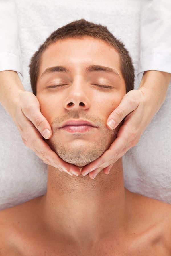 Young man receiving facial massage stock image