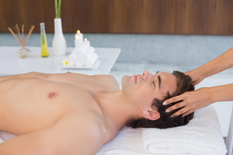 Young man receiving head massage at spa center. Side view of a handsome young man receiving head massage at spa center royalty free stock photos