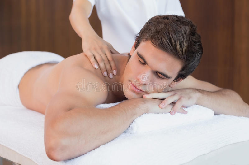Young man receiving shoulder massage at spa center. Close up of a handsome young men receiving shoulder massage at spa center stock photo