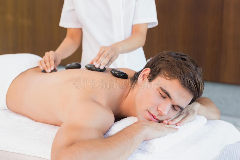 Young man receiving stone massage at spa center. Side view of a handsome young man receiving stone massage at spa center stock photo
