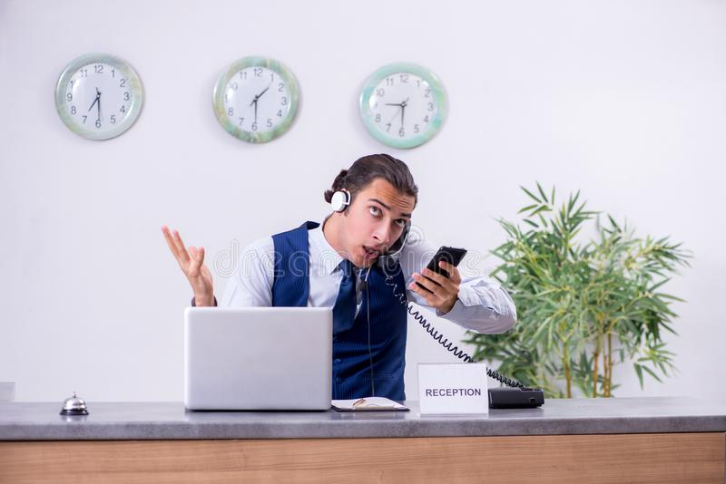 Young man receptionist at the hotel counter. The young man receptionist at the hotel counter royalty free stock image