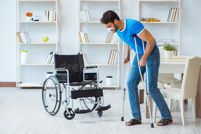 Young man recovering after surgery at home with crutches and a w. Heelchair royalty free stock photo
